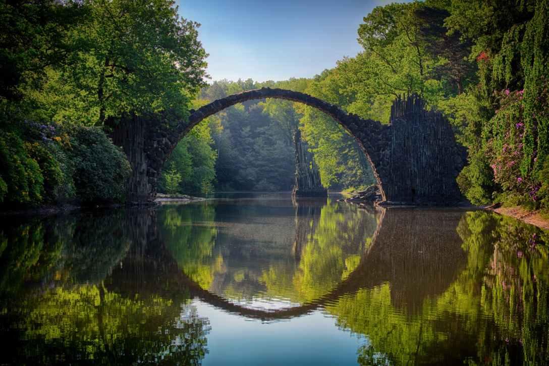 broken bridge reflected in river