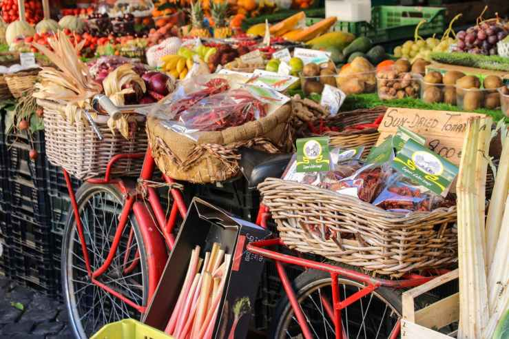 assorted fruits and vegetables in baskets for sale in the fruit market