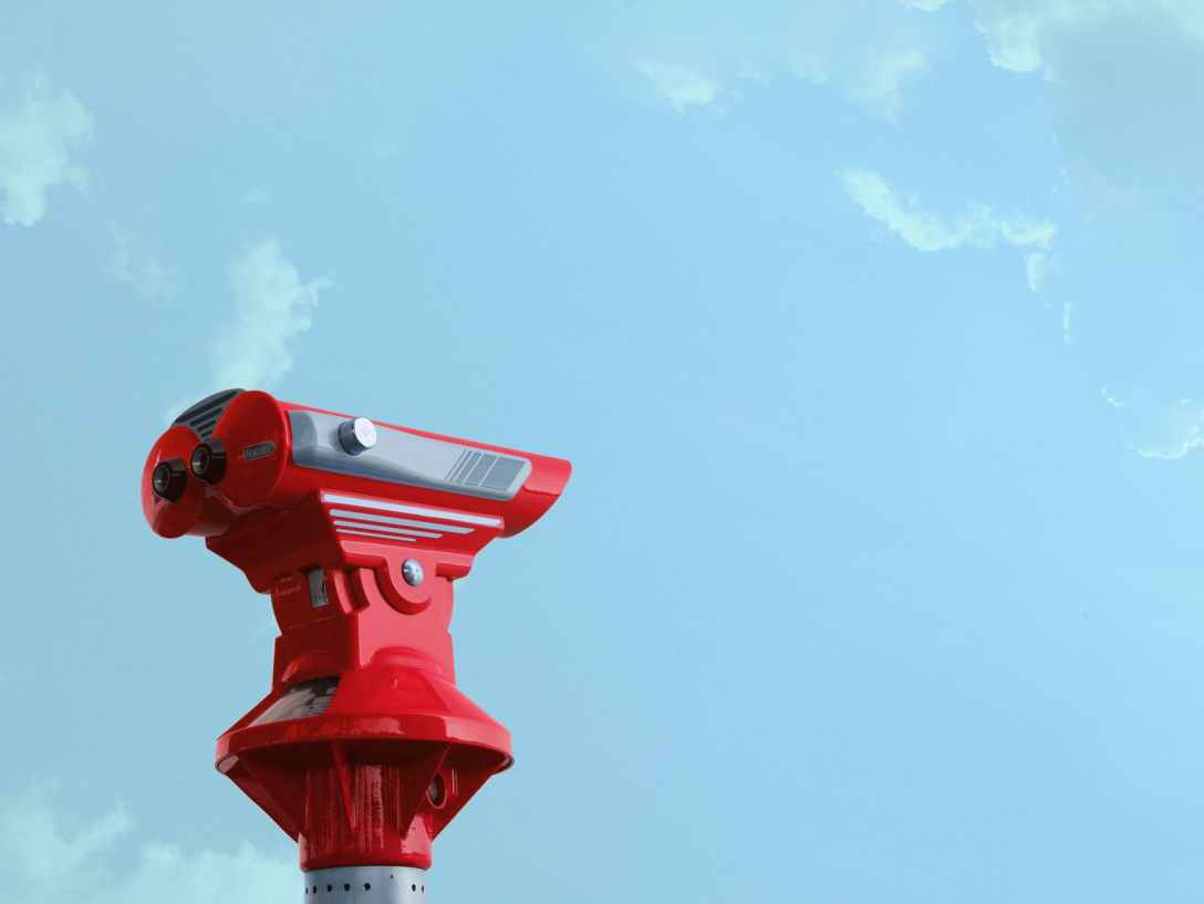 tourist binoculars against a blue sky